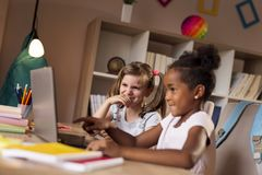 Little girls watching cartoons on a laptop computer. Two beautiful little girls sitting at a desk, watching cartoons on a laptop computer and having fun royalty free stock photo