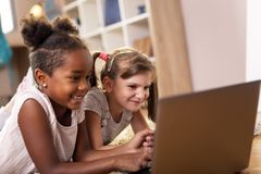 Little girls watching cartoons on laptop computer. Two little girls lying on the playroom floor, watching cartoons on a laptop computer and having fun. Focus on royalty free stock image