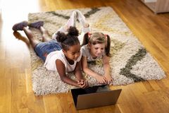 Little girls watching cartoons on a laptop computer. Two little girls lying on the playroom floor, watching cartoons on a laptop computer and having fun. Focus stock photos