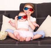 Little girls watching TV. Little cute sisters watching 3d TV Stock Images