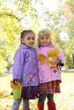 Little girls in waterproof coats and boots in autumn park Royalty Free Stock Photos