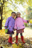 Little girls in waterproof coats and boots in autumn park Stock Photos