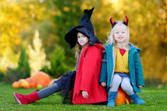 Little girls wearing halloween costume on a pumpkin patch Stock Images