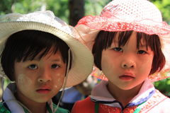 Little Girls Wearing Thanaka. Two little Burmese girls protects their faces from the harsh effects of the sun by slathering on some thanaka. Thanaka is a paste Stock Photography