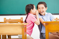 Little girls whispering and sharing a secret  in classroom Royalty Free Stock Photo
