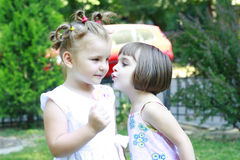 Little girls whispering to each other Royalty Free Stock Image