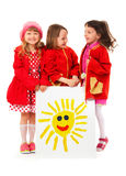 Little girls and white billboard of children's drawing of sunП Stock Images