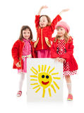 Little girls and white billboard of childrens drawing of sun Royalty Free Stock Images