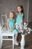2 little girls in white dresses sitting Royalty Free Stock Images