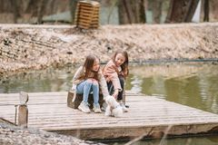 Little girls with a white puppy. A puppy in the hands of a girls. Little smiling blond girls sitting together hugging puppy on the lake royalty free stock photo