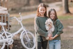 Little girls with a white puppy. A puppy in the hands of a girls. Little smiling blond girls sitting together hugging puppy in a park royalty free stock photo