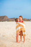 Little girls wrapped in towel after swimming at tropical beach. Cute little girls at beach covered with towel Royalty Free Stock Photo