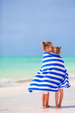 Little girls wrapped in towel after swimming at tropical beach. Cute little girls at beach covered with towel Stock Photo