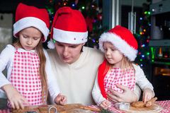 Little girls with young dad in Santa hat bake Royalty Free Stock Photo