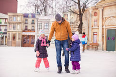 Little girls with young father enjoying skating Stock Photos
