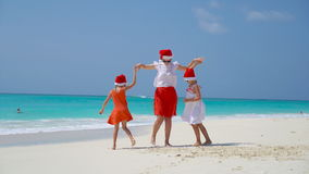 Little girls and young mother in Santa Hats on beach Christmas vacation stock footage