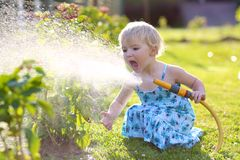 Little giving water to flowers in the garden Stock Photo