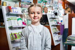 Little glad girl  in the pharmacy with parents and pharmacist Stock Photography
