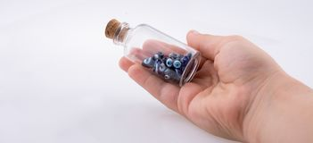 Little  glass bottle with blue evil eye beads in hand Stock Photography
