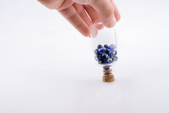 Little  glass bottle with blue evil eye beads in hand Royalty Free Stock Images