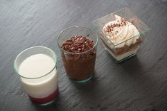 Little glass desserts on chalkboard background royalty free stock image