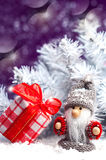 Little gnome with a red gift near spruce Royalty Free Stock Images