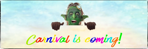 Little goblin looking across english text, carnival is coming Stock Photo