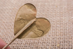 Little gold color heart shape in hand Royalty Free Stock Photos