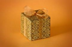 Little gold gift. Isolated on orange background Stock Photography