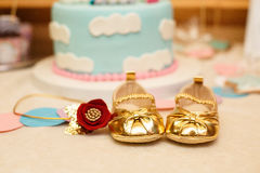 Little golden girl`s booties on background of Birthday cake. Royalty Free Stock Photo