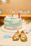 Little golden girl`s booties on background of Birthday cake. Stock Photography