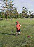 Little Golfer. Four year old boy on the golf course on a bright high contrast da royalty free stock photography