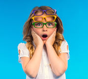 Little good girl. Portrait of a little girl with glasses isolated on a blue background Royalty Free Stock Photo