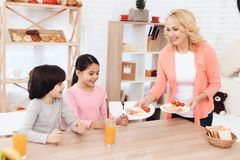 Little grandchildren sit in kitchen and wait for beautiful grandmother to bring dinner. Happy grandmother prepared breakfast for her grandchildren royalty free stock images