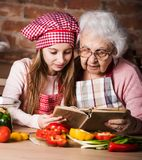Granddaughter reading recipe book with granny. Little granddaughter reading recipe book with her granny sitting at kitchen Stock Photography