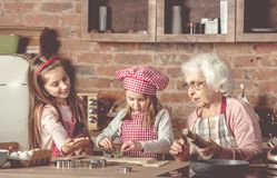 Little granddaughters help granny to bake cookies Royalty Free Stock Images