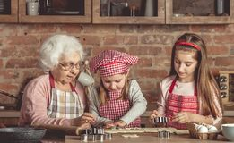 Little granddaughters help granny to bake cookies Royalty Free Stock Photos