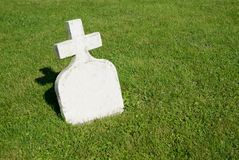 The Little Gravestone. A small white gravestone, topped with a simple cross, stands in the sunshine against a lush green lawn royalty free stock photography