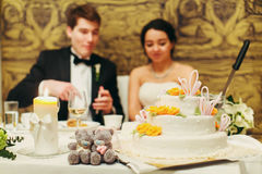 Little gray teddy bears stand on the table behind a wedding cake.  Stock Image