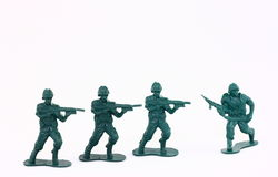 Little Green Army Men / Toy Soldiers. Four toy soldiers photographed on a white background. These little green army men illustrate many concepts from childhood Royalty Free Stock Images