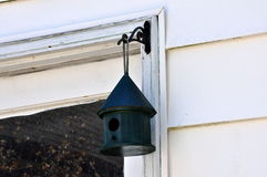 Little Green Birdhouse. A small wooden birdhouse hangs from a door frame Royalty Free Stock Image