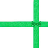 Little green bow knot on two crossing satin ribbon Stock Images