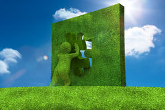 Little green character resolving a puzzle Stock Image
