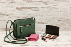 Little green ladies handbag, pink purse, eyeshadow palette and lipstick on wooden background. fashion concept Royalty Free Stock Images