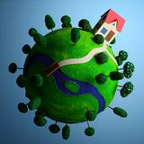 Little green planet with toy house. Royalty Free Stock Photo