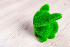 Little green rabbit on wooden floor, made from artificial grass Stock Photo