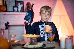 Little Guest of Halloween Party. Cute little boy wearing skeleton costume holding candle in hand while looking at camera with warm smile, interior of living room Royalty Free Stock Photos
