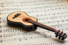 Little guitar lying on sheet music 7 Royalty Free Stock Photo