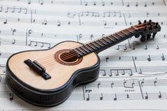 Little guitar lying on sheet music 6 Stock Image