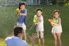 Little guys using water guns to spray their father. In the park royalty free stock image